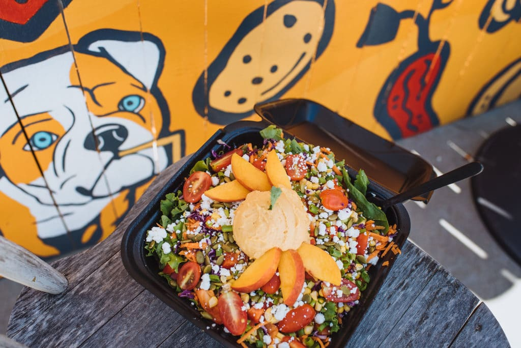 The food at Crave Food Truck is as beautiful as it is delicious. Check out this salad with goat cheese, hummus, and peaches.